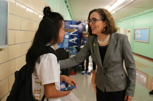 Oregon Gov. Kate Brown talks with a student at Madison High School in Portland.