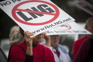 Protesters use signs to shield themselves from the rain during a rally before the Oregon LNG permit public hearing.
