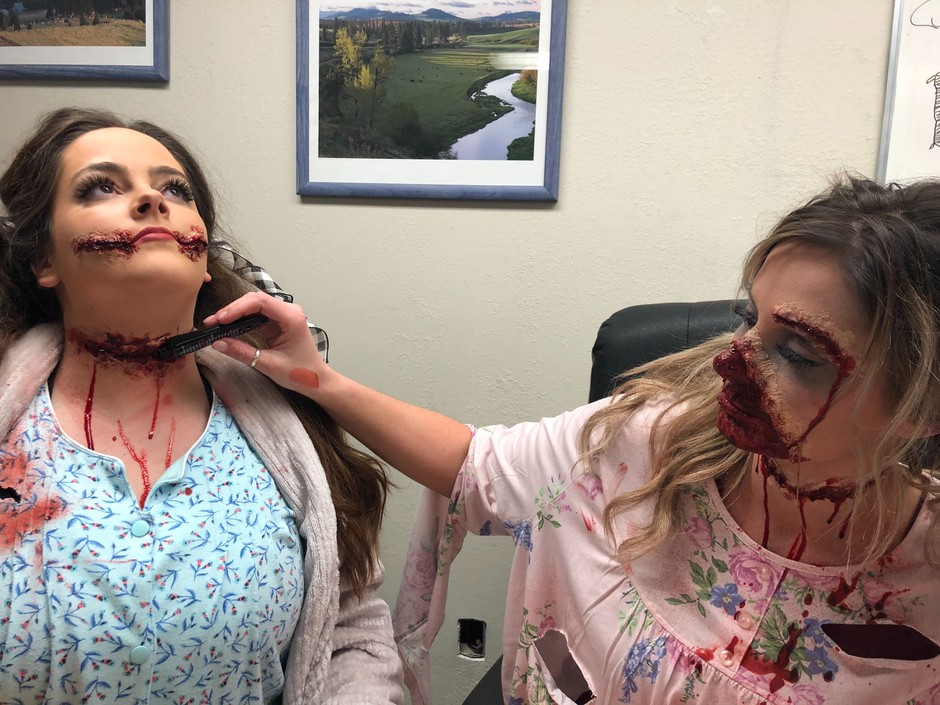 """Megan Chandler of Clarkston helps her friend Shelby Buttars add a bit more fake blood to her fake wounds in the city council chamber before going out to scare patrons of Haunted Palouse. They call themselves a """"slumber party gone wrong."""" They were putting on makeup in the city council chambers before going out to scare patrons at Haunted Palouse."""