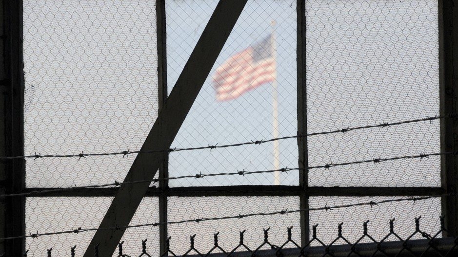 An NPR investigation finds that the military court and prison at Guantánamo Bay, Cuba, have cost taxpayers billions of dollars, with billions more expected. Above, an American flag is seen through the war crimes courtroom at the U.S. naval base at Guantánamo Bay on Oct. 17, 2012.