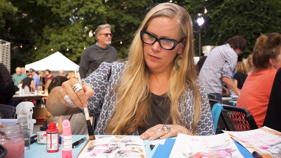 Jennifer Gilla Cutshall, owner of Verum Ultimum Art Gallery, works on her art work in front of a live audience at the Monster Drawing Rally.