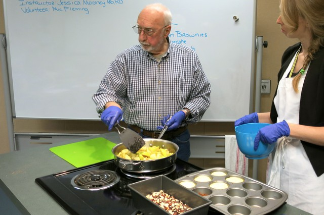 Ray Spaulding cooks apples them in front of a class at the Portland VA. Standing next to him is Jessica Mooney, a clinical dietitian. About 80 percent of veterans are overweight and obese and another quarter have diabetes. Those numbers are higher than the national average for all Americans.
