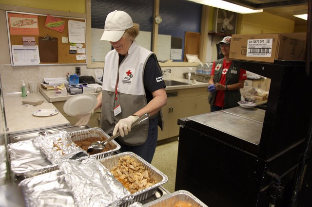 Staff serves food to Chetco Bar Fire evacuees at the Red Cross Relief Center, housed in an elementary school in Gold Beach, Oregon.