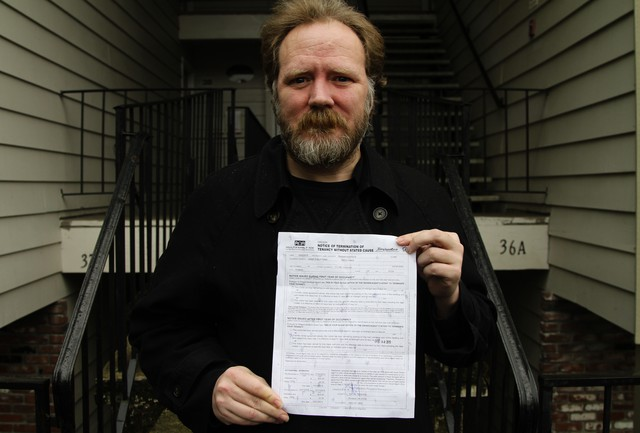 Navy Veteran Scottie Carpenter holds his notice of no-cause eviction.