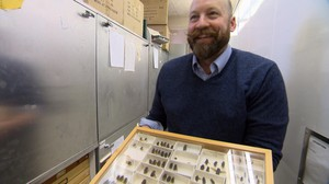 Chris Marshal showing off a tray of bot flies, like the one that developed inside his arm while he was a graduate student at Cornell University.