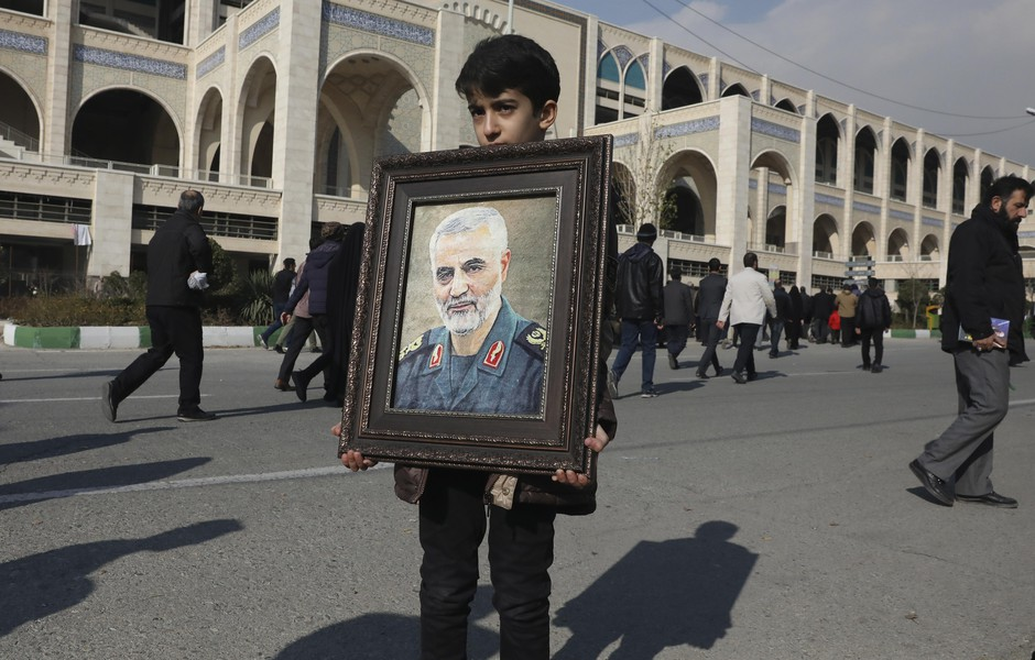 "A boy carries a portrait of Iranian Revolutionary Guard Gen. Qassim Suleimani, who was killed in the U.S. airstrike in Iraq, prior to the Friday prayers in Tehran, Iran, Friday Jan. 3, 2020. Iran has vowed ""harsh retaliation"" for the U.S. airstrike near Baghdad's airport that killed Tehran's top general and the architect of its interventions across the Middle East, as tensions soared in the wake of the targeted killing."