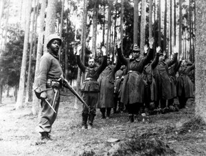 A  U.S. soldier of the 12th Armored Division stands guard over a group of Nazi prisoners captured in the surrounding German forest. April 1945.