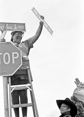 Co-chairs of the Martin Luther King Jr. Boulevard Renaming Committee Carolyn Leonard and Bernie Foster, publisher of the Skanner, switch out one of the Union Avenue street signs.