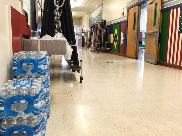 Bottles of water are piled next to a closed drinking fountain at Sabin Elementary School in Northeast Portland.