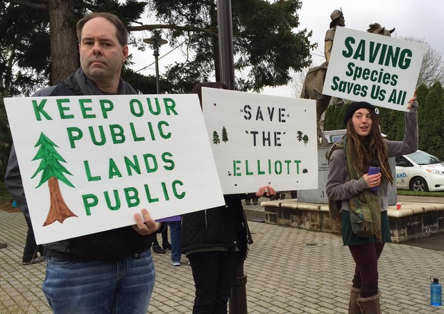 Opponents of a plan to sell the Elliott State Forest hold signs outside an Oregon State Land Board meeting.