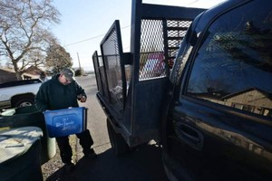 Horizon Project Inc. recycling pickup driver Dave Pauley checks a recycling container for non-recyclables while doing his morning route Tuesday, Feb. 13, 2018, in Milton-Freewater, Oregon.