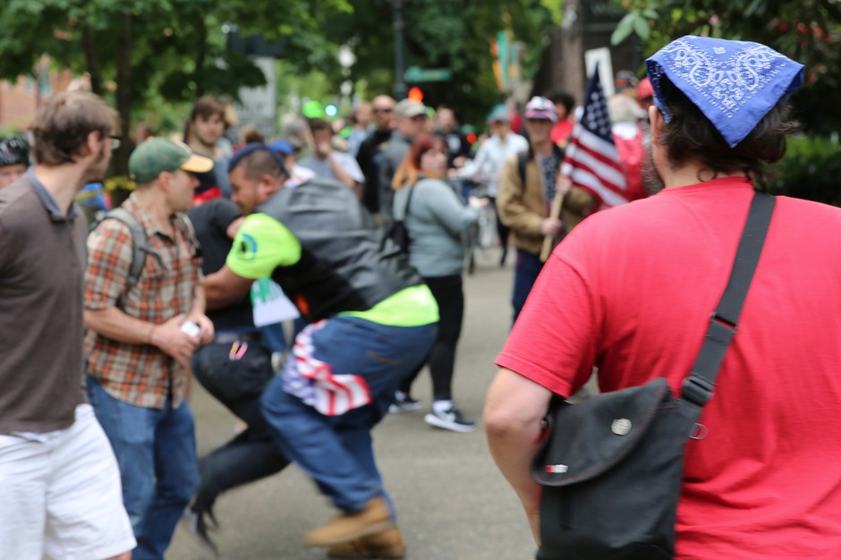 "In 2017, Tusitala ""Tiny"" Toese, center, a known member of the militia style group, the Oath Keepers, was photographed tackling an Antifa protester before federal law enforcement officers detained the protester and arrested him."