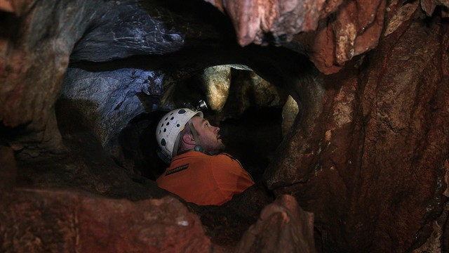 Neil Marchington peering into a hole in No Name Cave.