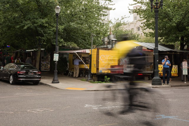 A bike whizzes by food pods on Southwest 10th Avenue and Alder Street in downtown Portland, Ore., on June 21, 2019. The pods must vacate the lot by the end of June to make room for a Ritz-Carlton.