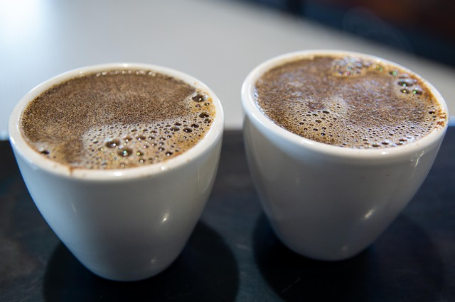 A crust develops on the top of a cup of coffee, trapping the coffee's aroma underneath.
