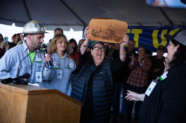 State Sen. Betsy Johnson, D-Astoria, holds up a wood cutting depcting the statehouse at a Timber Unity rally in front of the Oregon Capitol in Salem, Ore., Thursday, Feb. 6, 2020. Johnson opposes the cap-and -trade bill.