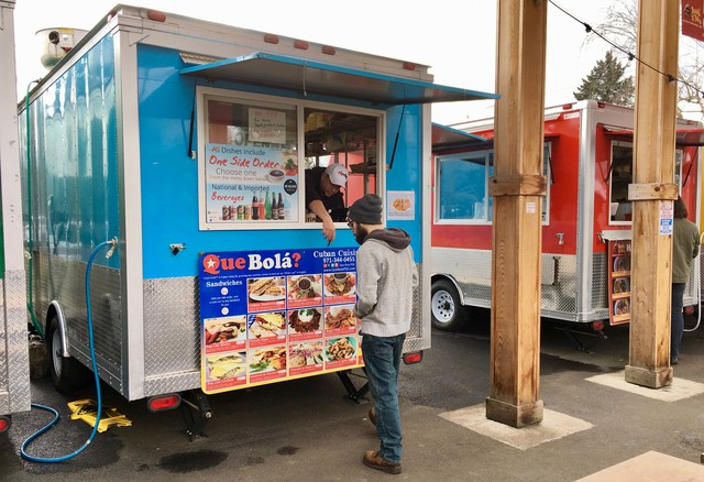 José Perez points out menu choices to a customer in front of his Cuban food cart, Qué Bola?, at the Portland Mercado in Southeast Portland.
