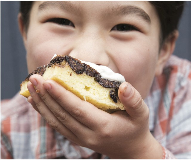 "Rachel Yang's older son, Pike Chirchi, 7, takes a bite of Upside-Down Fig Mochi Cake with Bleu Cheese Whip. The sweet-savory ""dessertish"" rice cake can be made with dried apricots instead of Mission figs."