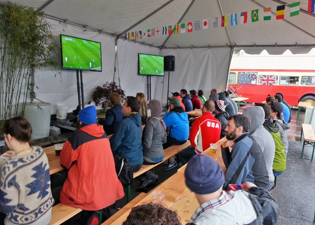 Soccer fans enjoy a match under the newly erected tents that shield patrons from the rainy weather.