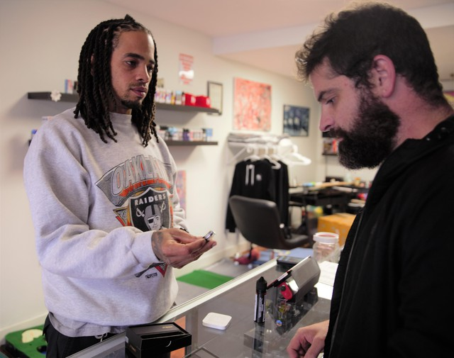 Rose City Vapors owner Marcus Nettles (left) works with customer Matt Menard at his shop in Northeast Portland.Nettles said Oregon'sflavored vaping ban will cost him business to the internet.