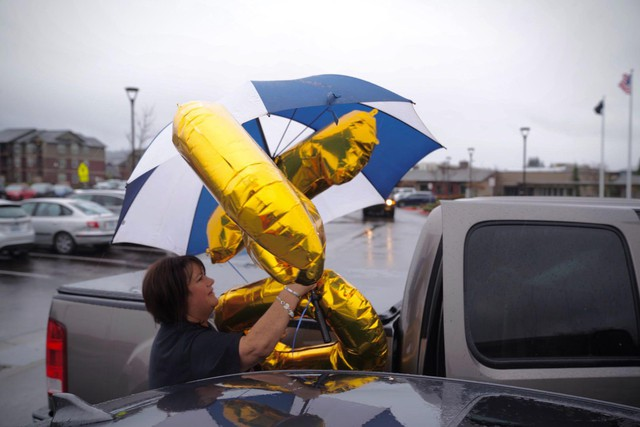 Jamie Yutzie unloads balloons from her car. Yutzie's grandfather, Bill Lapschies, survived the coronavirus to celebrate his 104th birthday.