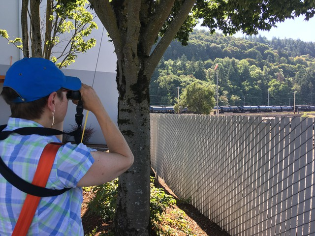 Climate activist Melanie Plaut, who's part of the group 350PDX, looks through binoculars at a row of tanker cars to determine what they're carrying.