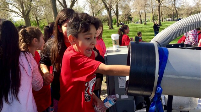 Victor Susunaga Castellanos, a fourth-grader at Westgate Elementary School, puts his hand inside the salmon cannon. The salmon cannon sucks fish up and over obstructions — like dams.