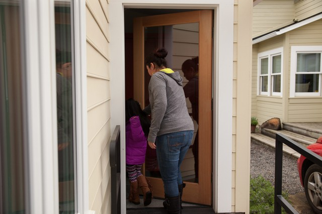 Michelle Labra and her daughter, Daphne, enter their home, an affordable dwelling unit in their landlord's backyard.