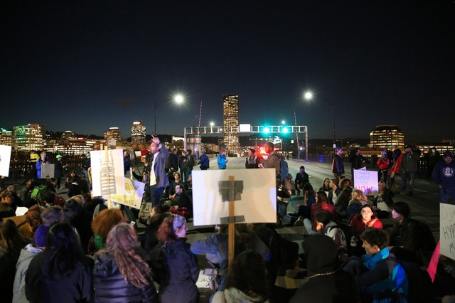 Portland high school students stage a sit-in on the Burnside Bridge, as part of a march in opposition to President-elect Donald Trump.