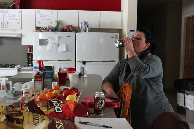 "Melissa Cooper chugs an energy drink while planning the next meal. Cooper is in charge of sorting supplies, cooking, and setting up new arrivals with a place to sleep. ""I'm tired. I'm getting four hours of sleep a night,"" she said."