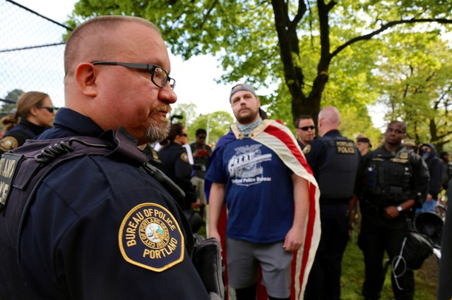 "Jeremy Joseph Christian (center wearing American flag), the man accused of a fatal stabbing on the MAX train, attended the April 29 ""March for Free Speech"" on 82nd Avenue."