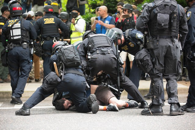 Portland police arrest a protester who skated past a police barricade during an afternoon of protests in downtown Portland on Sunday, June 4, 2017.
