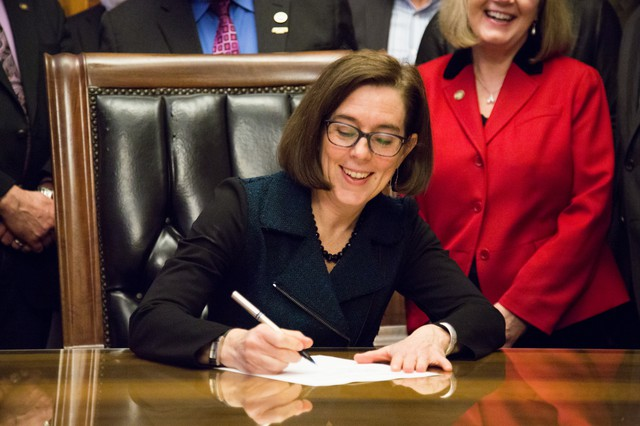 Oregon Gov. Kate Brown signs a bill into law to increase the state minimum wage in March 2016.