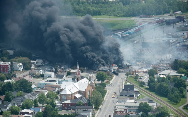 Smoke rises from railway cars that were carrying crude oil after derailing in downtown Lac Megantic, Quebec, Canada, July 6, 2013. A large swath of Lac Megantic was destroyed after a train carrying crude oil derailed, sparking several explosions and forcing the evacuation of up to 1,000 people.