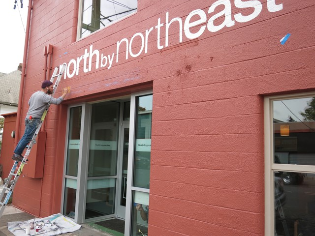 A sign writer adds the finishing touches to the newly opened North By Northeast Community Health Clinic.