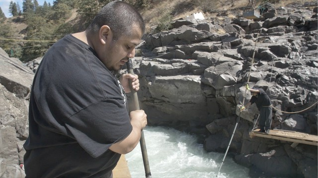 James Kiona Jr. uses a dip net to fish for salmon on one of the scaffolds at Lyle Falls.