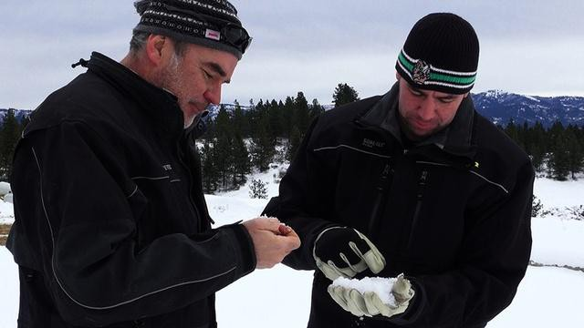 Idaho Power's Derek Blestrud and Brandal Glenn study the type of snow that's falling as a result of cloud seeding.