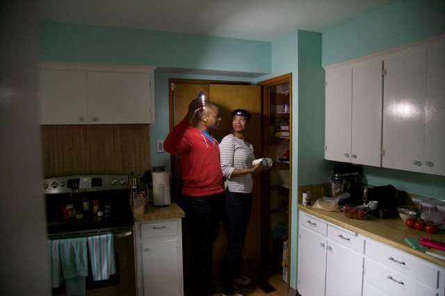 "Sara and Ed Johnson shine a flashlight in their pantry to see what they can make for their first ""Living Off Your Quake Kit"" dinner. The Johnsons have a flashlight in each room of their house."