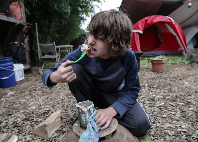 Shea Stephens eats a pancake cooked in a tin can on a fire in the backyard of their house in North Portland. Over the weekend, the Stephens had to live off what they could find and cook, without using power sources or running water.