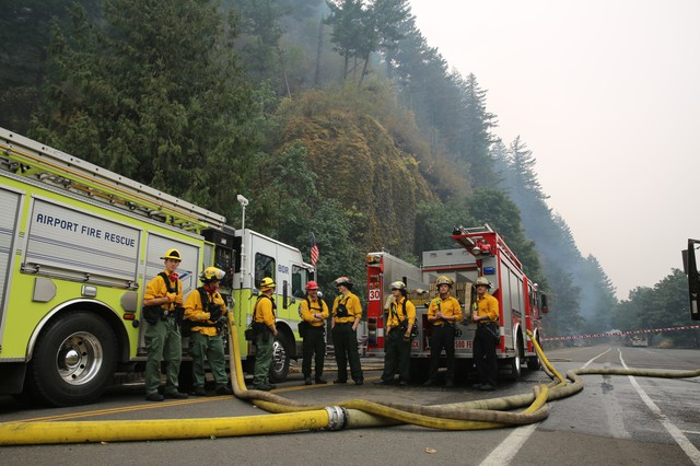Fire crews from different parts of the state rest at the bottom of Multnomah Falls where they worked to prevent the Multnomah Falls Lodge from burning on Sept. 6, 2017.