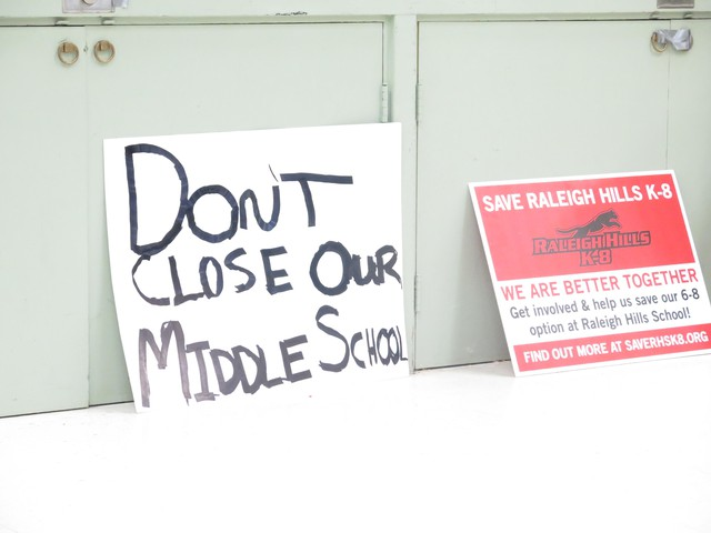 Signs made by members of the Raleigh Hills community ask Beaverton district officials to keep the school as a K-8.
