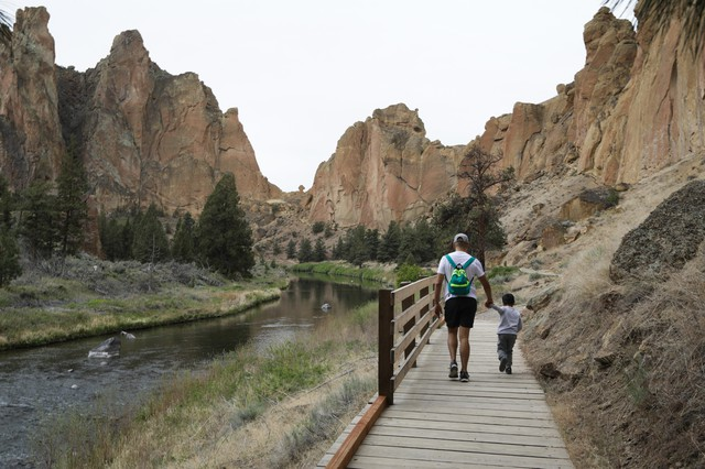 A man walkshand-in-hand with a small boy in Smith Rock State Park on May 16, 2020.