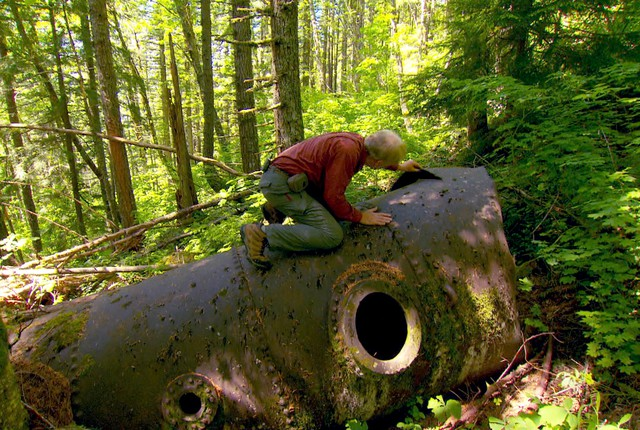 Don Nelsen climbs atop a 16-foot long boiler he found lying in the forest.