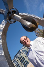 """Keith Lachowicz stands in front of """"Pod,"""" the 11-year-old steel, titanium and bronze sculpture in the traffic triangle across from Powell's Books on West Burnside Street. Lachowicz is the public art collections manager for the Regional Arts & Culture Council."""
