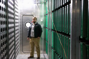 Project manager Steven Simonson stands in a new air handler at Harriet Tubman Middle School.