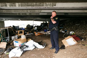 Salem Police Officer Bob Owings surveys what's left of a homeless camp under the Highway 22 overpass that crosses Mill Creek near Costco and Lowe's Jan. 29, 2019.