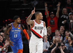Portland Trail Blazers guard Damian Lillard, right, reacts after making a basket as Oklahoma City Thunder forward Paul George, left, trails the play during the first half of Game 1 of a first-round NBA basketball playoff series in Portland, Ore., Sunday, April 14, 2019.