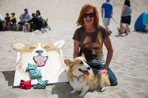 Linda Kay poses with her corgi Wallace next to a corgi-themed cornhole board while wearing a shirt with a corgi printed on it at the 2016 Oregon Corgi Beach Day in Cannon Beach.