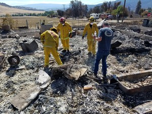 Cal Fire crews assist a homeowner who lost his home in Hornbrook, California to the Klamathon Fire.