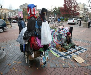 """A visitor hauls a cart full of belongings through downtown Eugene (left) past another visitor asking for money for """"laundry and vegan food"""" at Broadway and Willamette last November."""